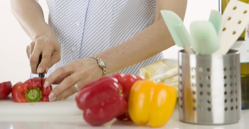 Woman cutting red and yellow peppers